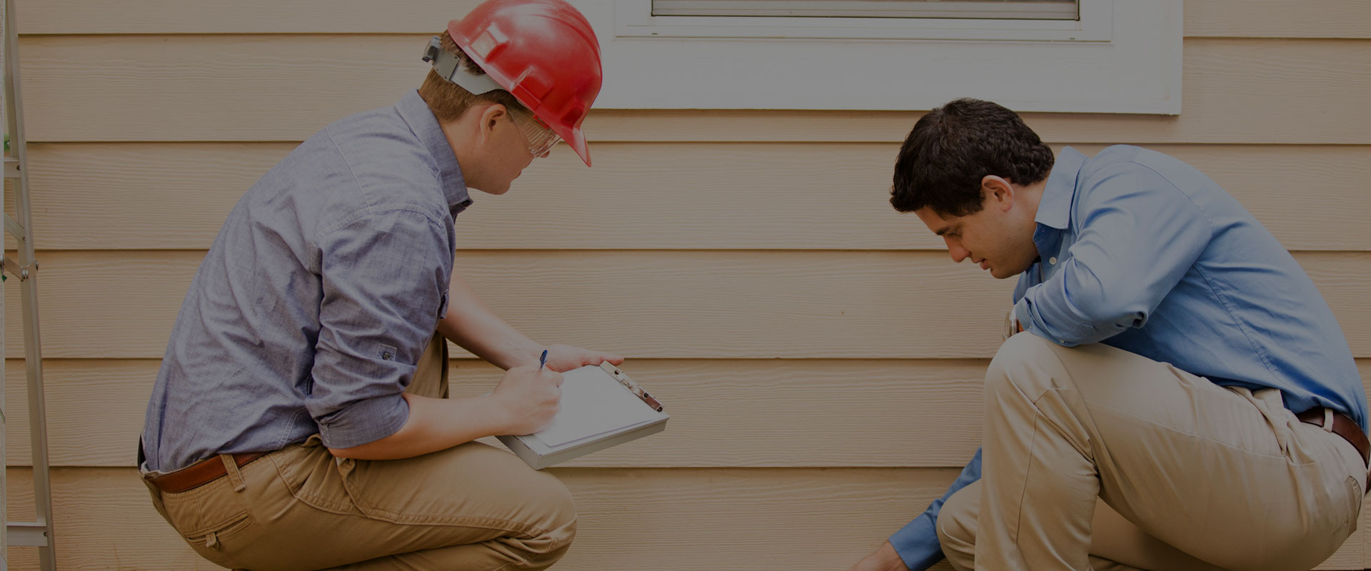 two men inspecting a homes foundation